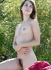 Young hippie Girl plays nude by the river bank