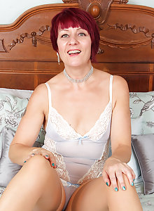 Redhead Mature babe Penny Brooks takes off her sexy lingerie to spread her pussy