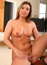 Long haired MILF fingers her neatly trimmed love canal in here